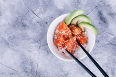 poke in a bowl on a marble table with black chopsticks