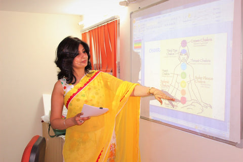 Woman teaching about the seven chakras on a white board
