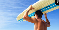 Male surfer holding surfboard with blue sky in background
