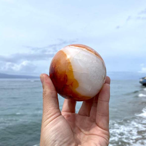 three inch carnelian sphere in front of the ocean