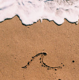 Hawaii beach with design in sand and ocean showing
