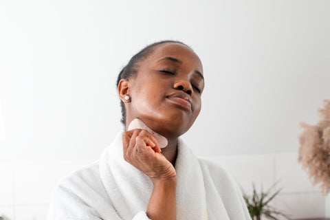 Woman rubbing healing crystal on face