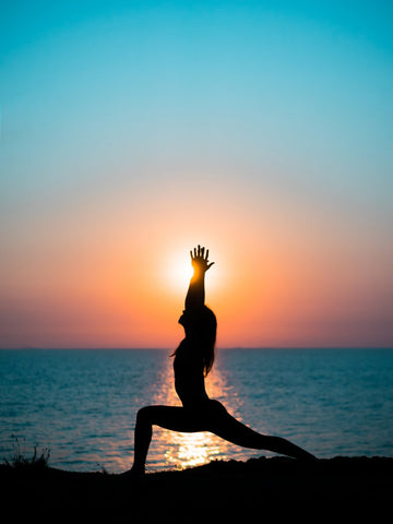 Woman in the Warrior pose in front of a sunset