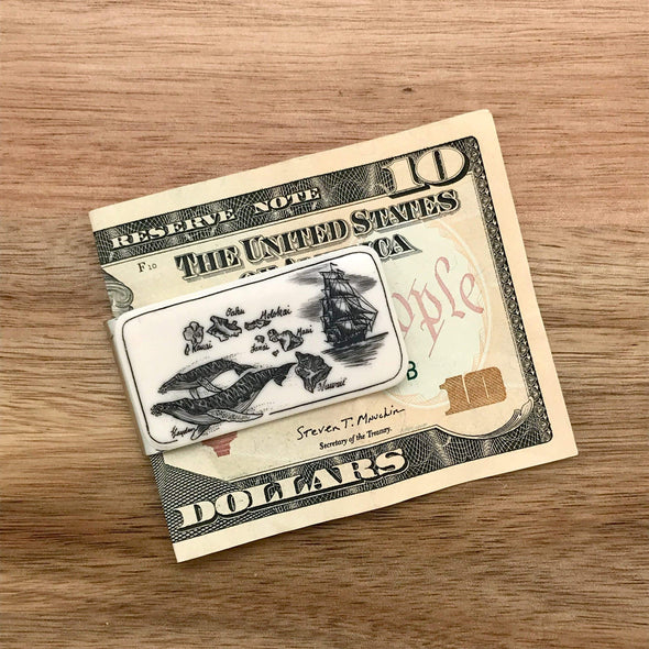 Scrimshaw Style Wide Money Clip featuring humpback whale, Hawaiian islands and ship detail designed by artist Linda Layden with money for size comparison. Money not included with purchase.