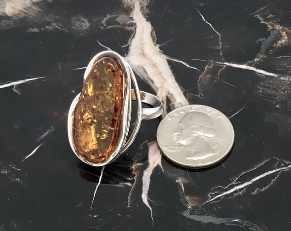 Rich honey Baltic Amber piece set in 925 sterling silver. The ring is a size of 9 1/2. Shown with a US quarter for size comparison.  - BAR001