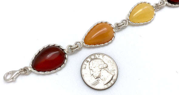 "Beautiful teardrop Baltic Amber bracelet.  Alternating colors of amber are framed in 925 Sterling silver.  This bracelet measures 9""-9.5"" and secures with a lobster claw style clasp. Shown with US quarter for size comparison."