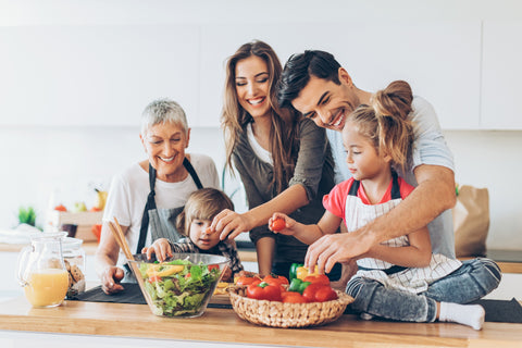 Family in front of salad and other veggies