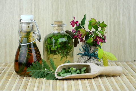 Herbs in solution and a wooden scoop with herbs in it