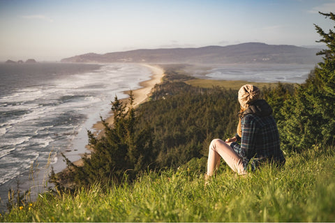 Woman sitting in nature overlooking the ocean