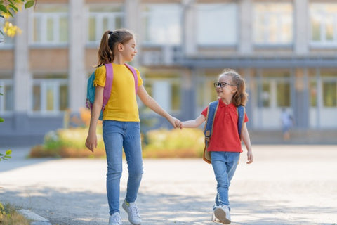Two girls walking hand in hand back to school