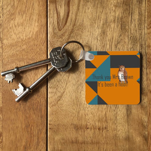 "An orange, teal and grey key ring on a table. The key ring has a personalised message reading ""thank you Mrs Brown, its been a hoot!"" and an illustration of an owl."