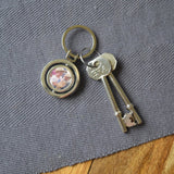 A personalised circular keyring with a spinning section. The keyring is personalised with a family photo.