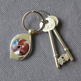 A personalised teardrop shaped metal keyring. The keyring is on a table. It has been personalised with a family photo.