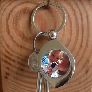 A metal keyring with a personalised photo in the centre. The keying is silver coloured metal and is in a teardrop shape.