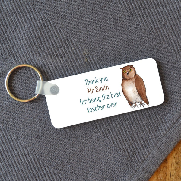 "A rectangular key ring on a wooden table. The key ring has a personalised design printed on it which includes an illustration of an owl and a message reading ""thank you Mr Smith for being the best teacher ever"""