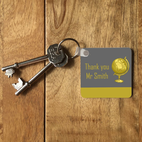"A personalised keyring on a table with a set of keys. The keyring is square and the design is grey and yellow. The design includes a yellow globe and the message ""thank you Mr Smith"""