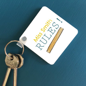 "A square key ring on a blue table with a personalised design. The design includes a message which reads ""Miss Smith Rules!"" and an illustration of a ruler. The text is yellow and teal."