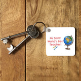 "a personalised square key ring on a set of keys, the design on the key ring includes a globe and the message ""Mr Smith, world's best teacher"""