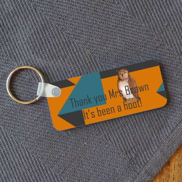 "A rectangular keyring on a table with a personalised design. The design includes an illustration of an owl and a message reading ""thank you mrs brown, its been a hoot!"" the design is on an orange, teal and grey background."