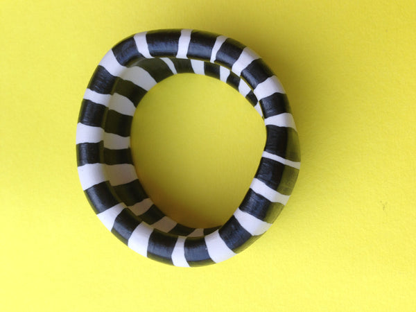 Aerial view of black and white striped porcelain bangle by Yvette Eady, on yellow background