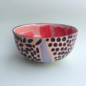 Glazed colourful ceramic bowl front view – with black spots and dashes and flashes of pastel colours on the exterior and pink and red glazed design on the inside