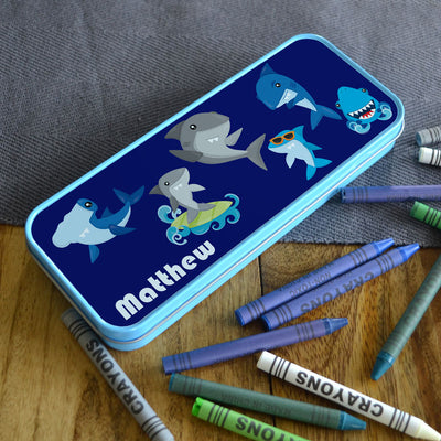 A personalised blue pencil case with a shark design printed on it and a name in white lettering