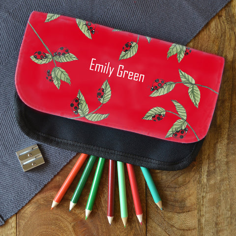 "A red personalised ladybird pencil case. The pencil case is personalised with the name ""Emily Green"" and is on a table next to some coloured pencils."