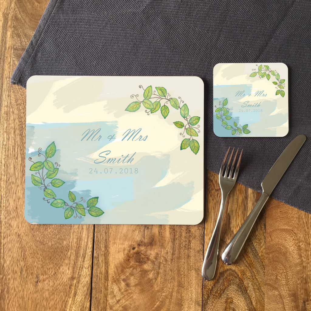 A personalised placemat and coaster on a table next to a knife and fork. The coaster and placemat feature a watercolour design with a leaf pattern
