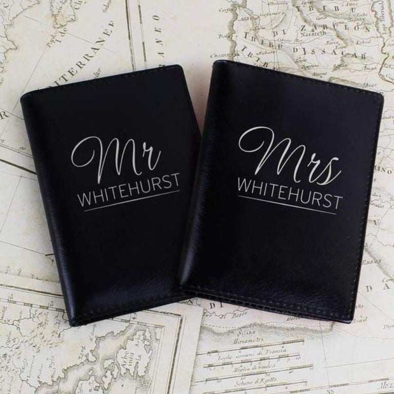 "2 black leather personalised passport holders, the messages read ""Mr Whitehurst"" and ""Mrs Whitehurst"""