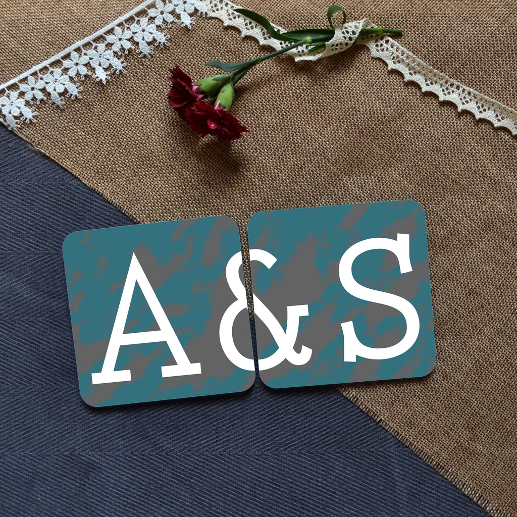 "A photo of 2 personalised square coasters which when placed next to each other complete the message ""A&S"""
