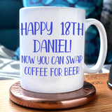 "A personalised 18th birthday mug with blue text reading ""happy 18th Daniel, now you can swap coffee for beer"""