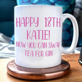 "A personalised birthday mug with the message ""Happy 18th Katie, now you can swap tea for gin"" in pink writing"