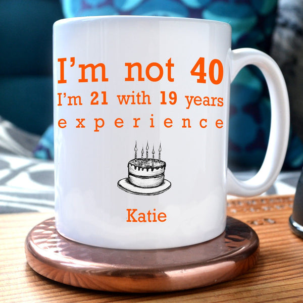"A personalised white mug with the message ""I'm not 40 I'm 21 with 19 years experience"" printed in orange text and an illustration of a birthday cake underneath. Below the birthday cake is the name ""Katie"""