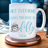 "A personalised white mug with the message ""Not everyone looks this good at 50"" printed in pale blue. There is an illustration of a birthday cake and below this the name ""Sarah"" is printed"