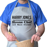 Close up of personalised house chef address apron in light grey with black lettering