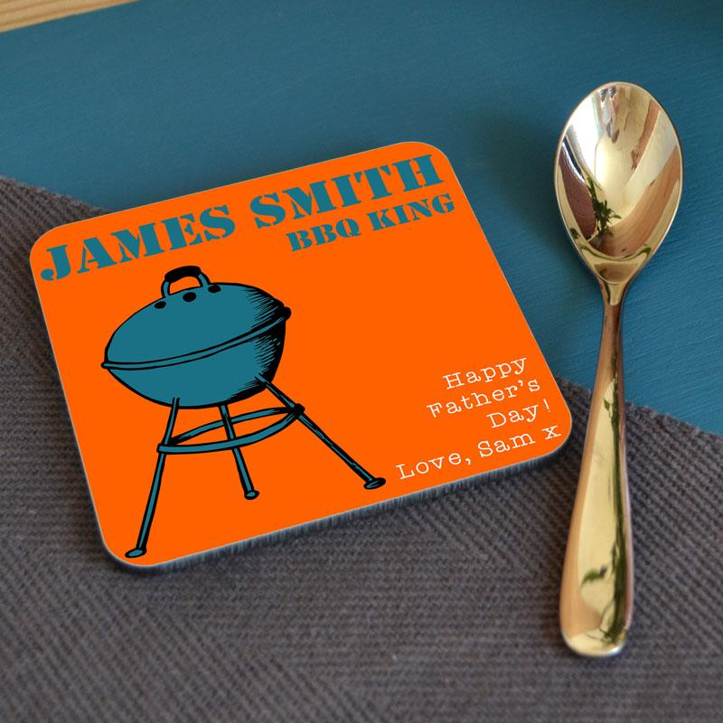 A personalised orange coaster with a blue BBQ and a custom message