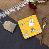 A personalised square yellow baking themed coaster on a table next to a tea spoon