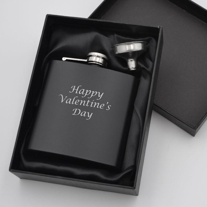 A personalised black hip flask in a black box with a black satin lining
