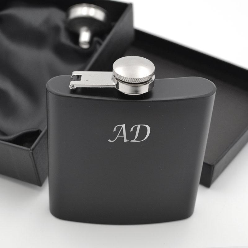 "A personalised black hip flask with the letters ""AD"" on it"