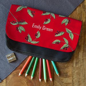 "A personalised red and black pencil case with a ladybird pattern. The pencil case is personalised with the name ""Emily Green"""
