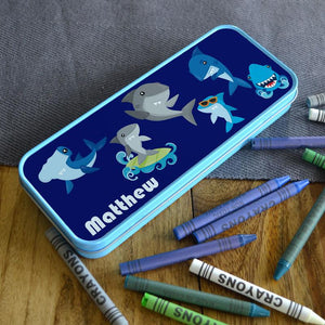 "A personalised blue pencil tin with a cartoon shark pattern printed on the lid with the name ""Matthew"" in white lettering"