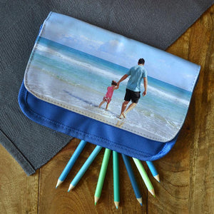 A personalised blue pencil case with a photo of a dad and daughter on the beach printed on it