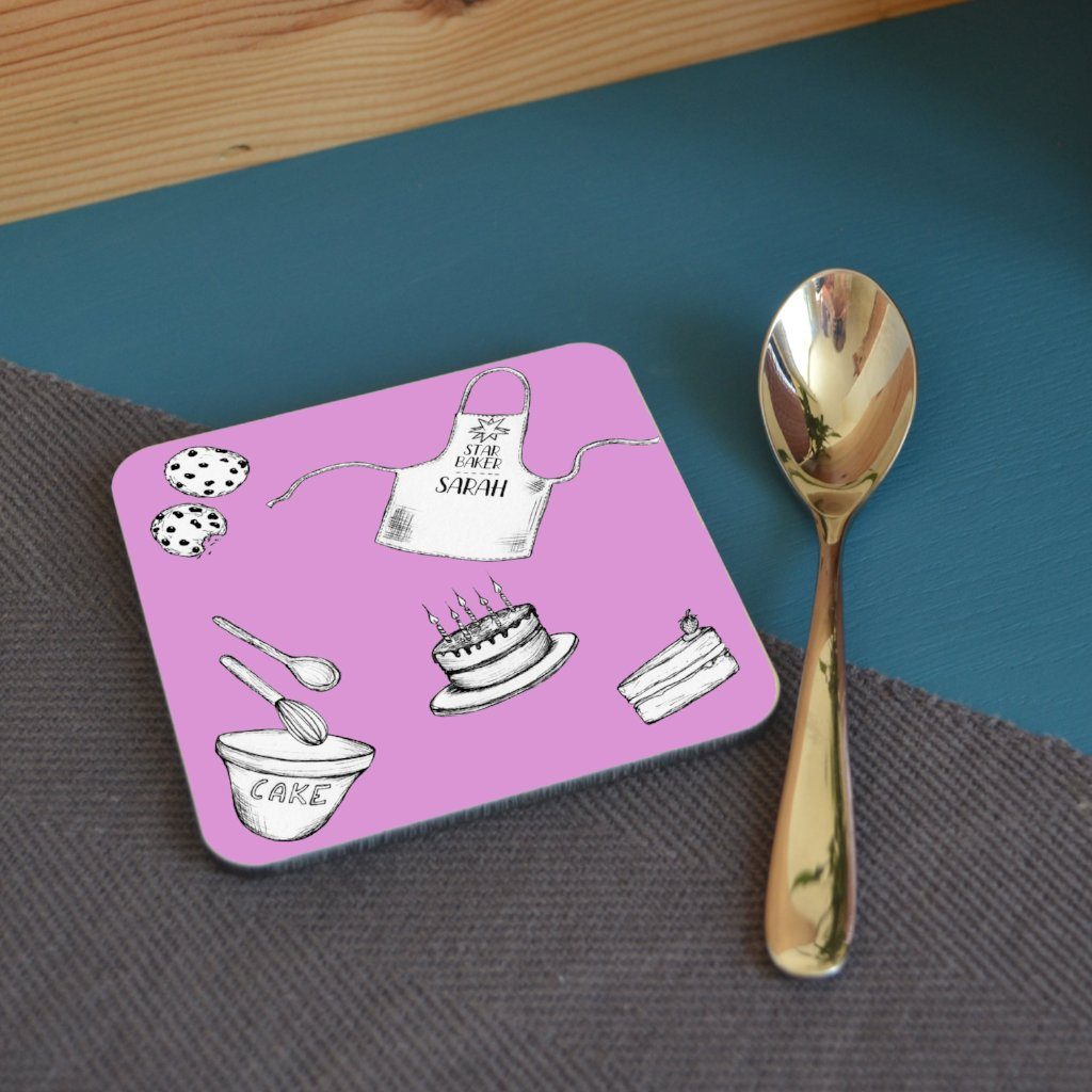 "A personalised pink square coaster with baking related illustrations and a personalised message reading ""star baker Sarah"" printed on the front of an apron"