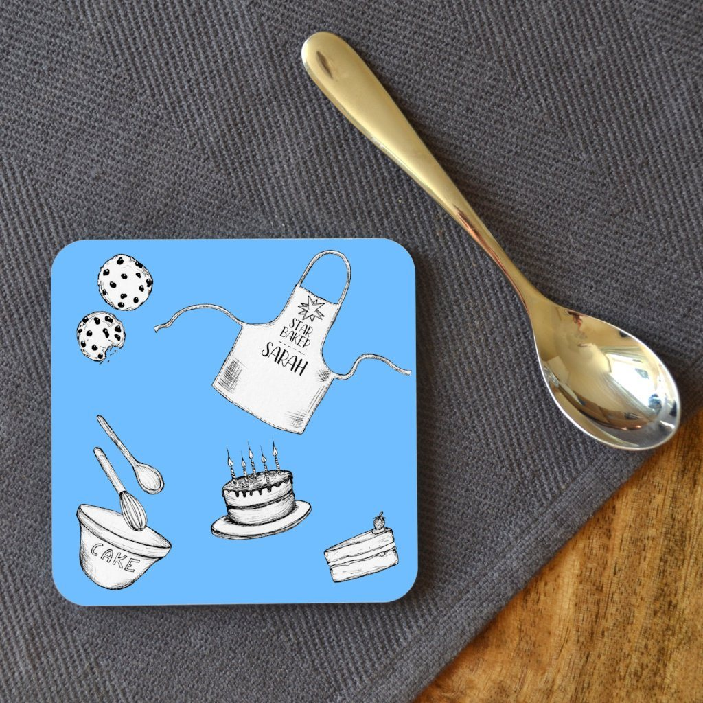 A personalised blue square coaster with illustrations of a cake, cookies, a mixing bowl and a personalised star baker apron