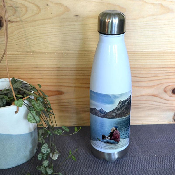 A personalised white bowling pin shaped water bottle with a photo of a man and woman stood by a lake printed on it.
