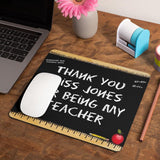 A personalised teacher mouse mat on a wooden desk. The mouse mat features a chalk board design.