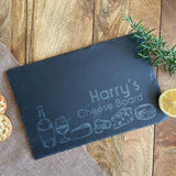 A personalised slate cheese board with engraved cheese icons and a custom name