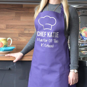 "Personalised chef apron in purple with white print, the design features a chef's hat and the words ""Chef Katie"""