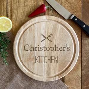 "A personalised wooden chopping board with a knife and fork icon and the words ""Christopher's Kitchen"""