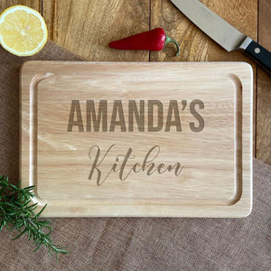 "Personalised wooden chopping board with the words ""Amanda's Kitchen"" engraved into the surface."